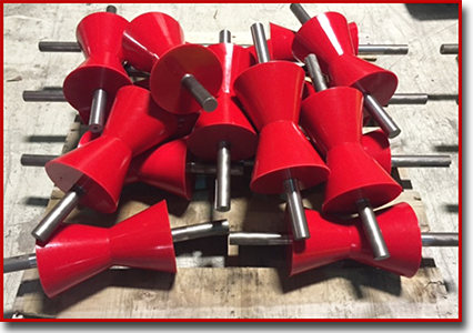 Several red Vee rollers on a pallet